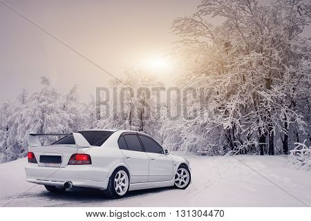 Saratov, Russia - December 06, 2014: White car Mitsubishi Galant VR-4 at countryside road at winter sunset