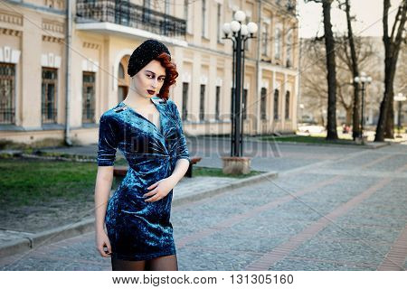 Beautiful young girl in blue dress posing on street over building background