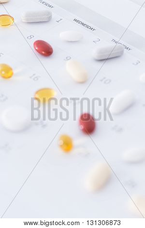 Close up of various pills lying on a white table