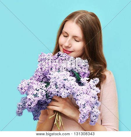 Cute Woman Enjoying Smell Of Bouquet Lilac Flowers Over Colorful Blue Background