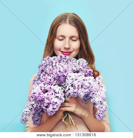 Happy Smiling Woman Enjoying Smell Of Bouquet Lilac Flowers Over Colorful Blue Background