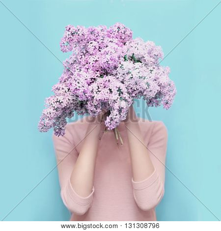 Woman Hiding Head In Bouquet Lilac Flowers Over Colorful Blue Background