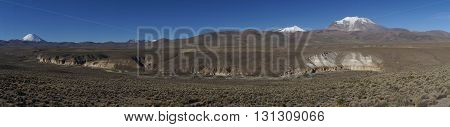 Panorama of the snow covered peaks of the Guallatiri volcano (6063 m) and Parinacota volcano (6342m) towering above the Altiplano and cliffs running along the valley of the River Lauca in Lauca National Park, northern Chile.