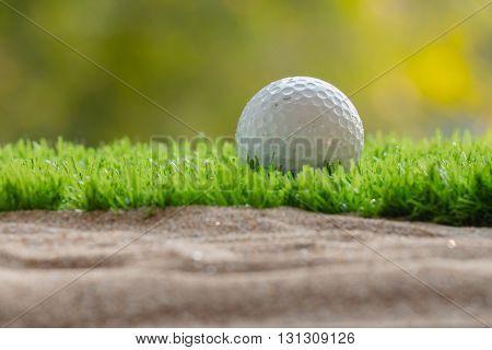 Golf ball on grass close sand bunker