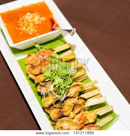 chicken satay barbecue and sauce on white plate.