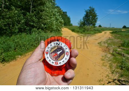 Before the fork with a compass. Hand with compass on background of the bifurcation of the path.