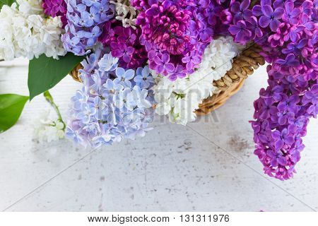 Bunch of fresh lilac colorful flowers in basket close up