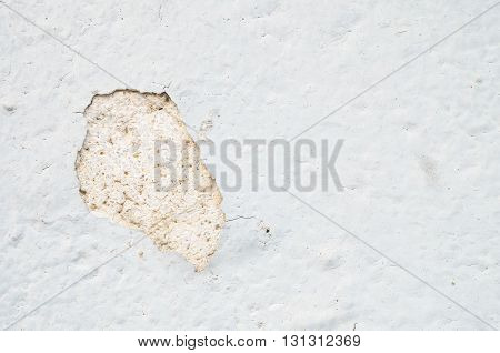 Closeup old and peeling white painted cement wall background