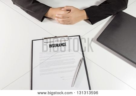 Businesswoman sitting with insurance form in front of her.