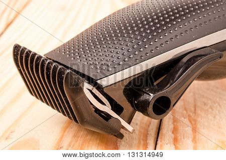 hair trimmer on a light wooden background closeup.