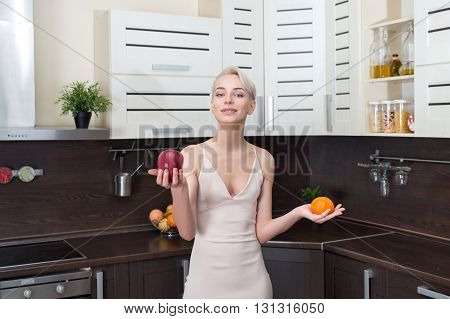 Portrait of beautiful girl holding apples and orange fruit her hands in modern kitchen.