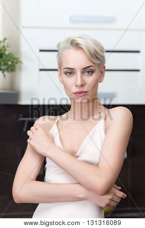 portrait of the blonde with short hair in modern kitchen