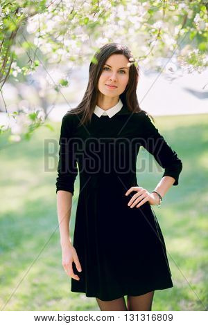 Beautiful young woman in casual wear in the flowering park