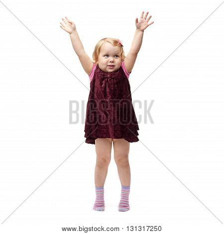 Young little girl with curly hair and hands in air in purple dress standing over isolated white background