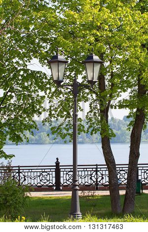 Old lantern on the banks of the river Volga in summer day