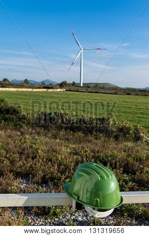 Wind turbines blades on the countryside and a green protection helmet