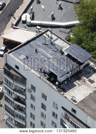 Moscow - 25 July 2015: Workers repairing the roof of an apartment house in the summer of July 25 2015 Moscow Russia