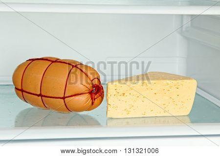 Fresh appetizing sausage and cheese on refrigerator shelf taken closeup.