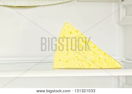 Fresh appetizing cheese on refrigerator shelf taken closeup.