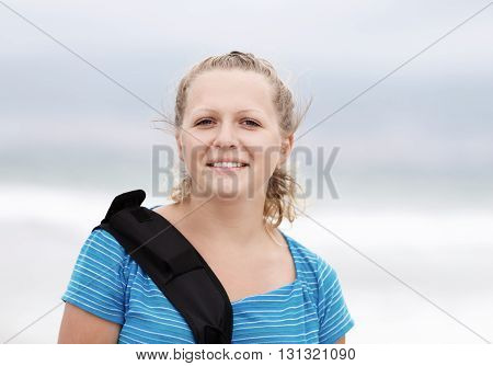 Photo of a smiling young blonde woman outdoor. Close-up of smiling girl. Selective focus on model.