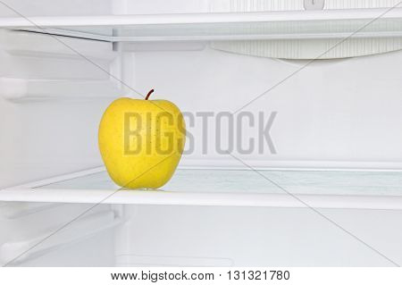 Lifestile concept.Yellow apple in domestic refrigerator taken closeup.