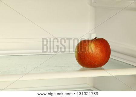 Ripe red apple in domestic refrigerator. Toned image.