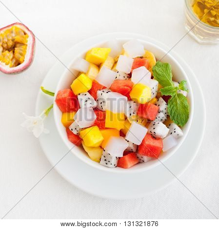 Bowl of fresh exotic fruit salad on white summer background Healthy breakfast Copy space Top view