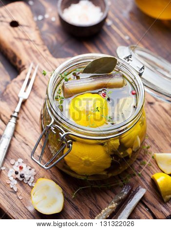 Marinated yellow pattypan summer squash, eggplant with herbs and spices in olive oil in a glass jar Wooden background
