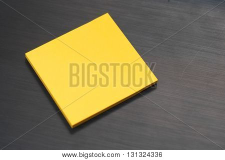 Yellow Post-It on a Black Textured Background