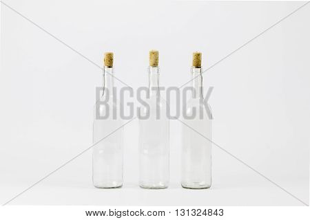 Three empty glass bottle with cork isolated on white background