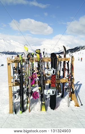 Les Arcs Alps France - March 13 2016: Skis and snowboards resting on a wooden stand on ski slopes near apres ski restaurant in French Alps.