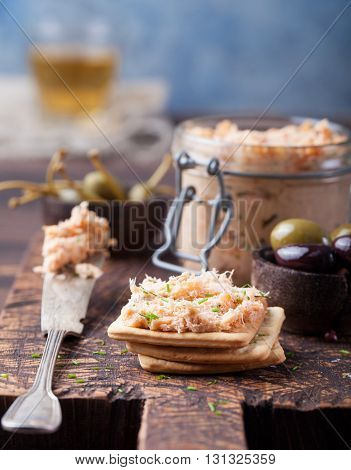 Smoked salmon and soft cheese spread, mousse, pate in a jar with crackers, olives and capers on a wooden background