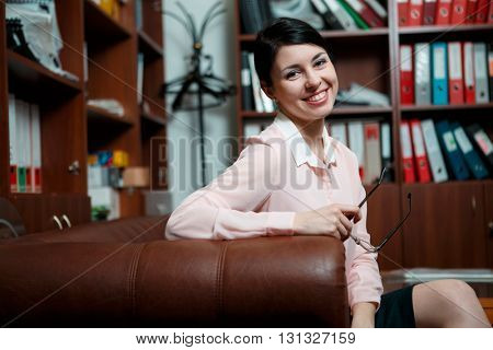 Business woman rests at leather sofa