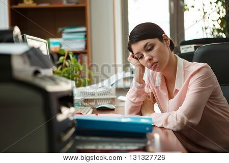Tired businesswoman sleeping on the desk.