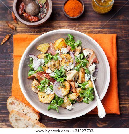 Potato salad with bacon, mushroom on orange napkin Wooden background