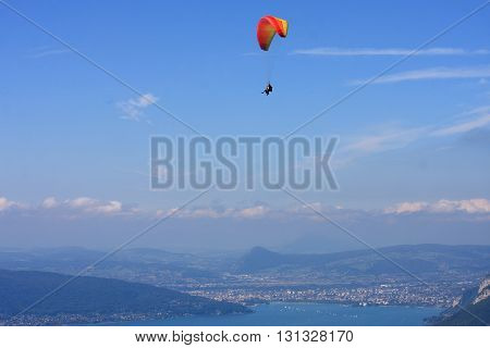 Paraglider flying high above Lake Annecy, France