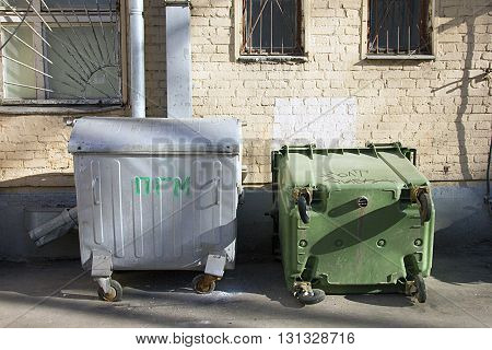 two old metal and plastic dumpsters in the yard of residential building