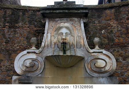 medieval roman marble fountain with funny bas-relief face in italian patio Rome Italy