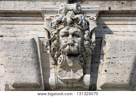 medieval roman stone sculpture on the wall of building in form of lion head with his tongue hanging out Rome Italy
