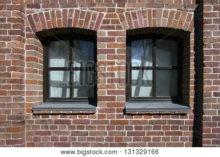 old red brick wall of building with two windows on street of Moscow at sunny weather