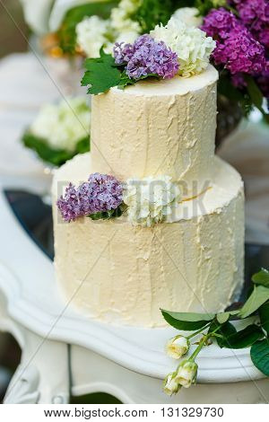The multilevel wedding cake with lilac on the table.