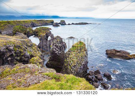 July day in Iceland. Magical coastal cliffs fishing village Arnastapi