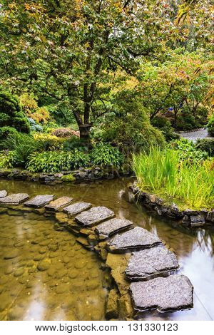 The track of stones in  water in Japanese part of garden. Decorative private garden on Vancouver Island in Canada - Butchart Gardens