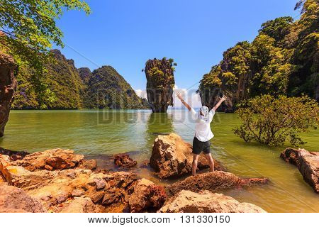 Exotic vacation in Thailand. Enthusiastic tourist threw his hands up