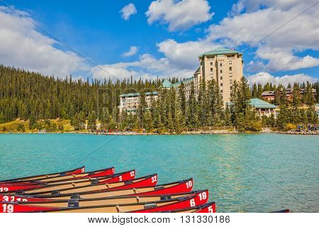 Lake Louise on a beautiful sunny day. At the pier moored red canoe for tourists. The lake is surrounded by pine forests