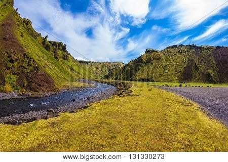 The road to the camping. Summer blooming Iceland. Pakgil Canyon - green grass and moss on the rocks. At the bottom of the canyon flows a small creek fast