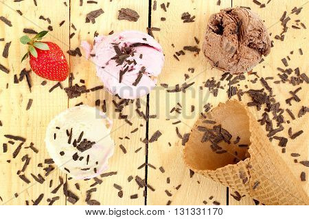 ice cream balls and cone on wooden surface