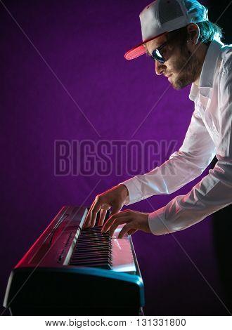 Man playing on electronic musical keyboard, close-up.