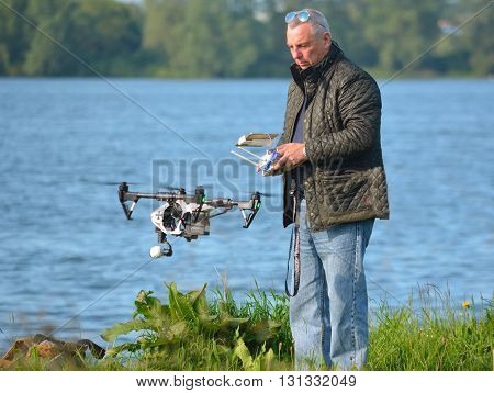 Grafham, Cambridgeshire, England - May 22, 2016: Man flying Drone, Drone in picture, water in background.
