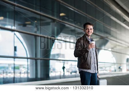 Stylish handsome young male traveller with bristle standing outdoors. Man wearing jacket and shirt. Smiling man looking to camera holding cup of coffee.